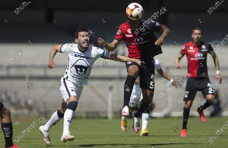 Pumas' Juan Vigon competes for the ball with Atlas' Anderson Santamaria during a Mexico soccer league match in Mexico City