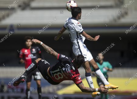 Atlas' Milton Caraglio, left, fights for the ball with Pumas' Jeronimo Rodriguez during a Mexico soccer league match in Mexico City