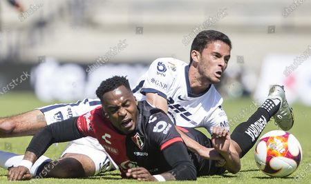 Pumas' Jeronimo Rodriguez (white) fights for the ball with Atlas' Alex Ibarra during a Mexico soccer league match in Mexico City