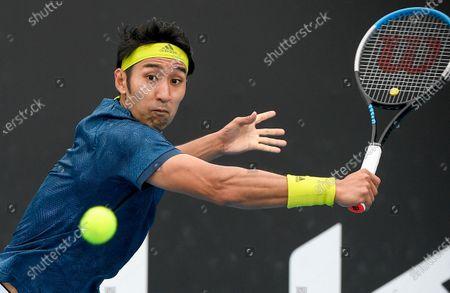 Stock Image of Japan's Yasutaka Uchiyama makes a backhand return to Slovenia's Aljaz Bedene during a tuneup tournament ahead of the Australian Open tennis championships in Melbourne, Australia