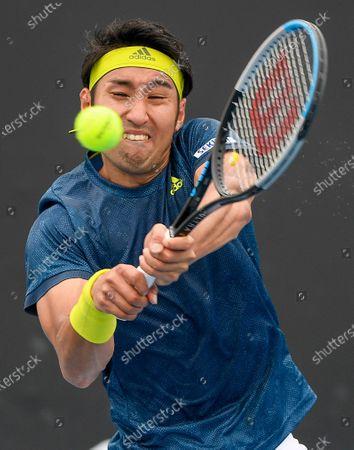 Japan's Yasutaka Uchiyama makes a backhand return to Slovenia's Aljaz Bedene during a tuneup tournament ahead of the Australian Open tennis championships in Melbourne, Australia