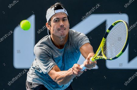 Stock Photo of Australia's Jason Kubler makes a backhand return to Italy's Lorenzo Sonego during a tuneup tournament ahead of the Australian Open tennis championships in Melbourne, Australia
