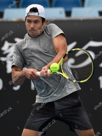 Australia's Jason Kubler makes a backhand return to Italy's Lorenzo Sonego during a tuneup tournament ahead of the Australian Open tennis championships in Melbourne, Australia