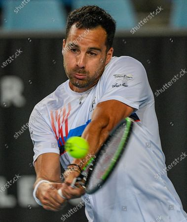 Salvatore Caruso makes a backhand return to compatriot Italy's Andreas Seppi during a tuneup tournament ahead of the Australian Open tennis championships in Melbourne, Australia