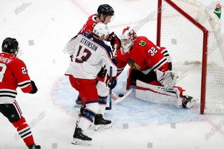 Chicago Blackhawks goaltender Kevin Lankinen (32) covers up a shot by Columbus Blue Jackets right wing Cam Atkinson (13) as Blackhawks defenseman Ian Mitchell, center, defends during the first period of an NHL hockey game, in Chicago