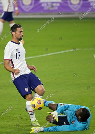 Trinidad and Tobago goalkeeper Adrian Foncette, right, blocks a shot by United States midfielder Sebastian Lletget (17) during the first half of an international friendly soccer match, in Orlando, Fla