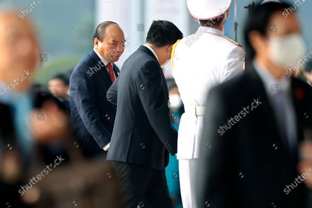 Vietnamese Prime Minister Nguyen Xuan Phuc, left back, arrives at the National Convention Center to attend the closing ceremony of the 13th National Congress of the Communist Party in Hanoi, Vietnam, . Vietnam's ruling Communist Party on Sunday reelected Nguyen to be its chief, the state Vietnam News Agency reported