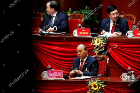 Vietnamese Prime Minister Nguyen Xuan Phuc, bottom, attends the closing ceremony of the 13th National Congress of the Communist Party of Vietnam at the National Convention Center in Hanoi, Vietnam, . Vietnam's ruling Communist Party on Sunday reelected Nguyen to be its chief, the state Vietnam News Agency reported