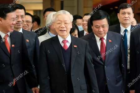Newly re-elected Vietnam Communist Party General Secretary Nguyen Phu Trong, center, leaves after a press conference at the closing ceremony of after the 13th National Congress of the Communist Party of Vietnam, in Hanoi, Vietnam