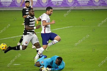 Trinidad and Tobago goalkeeper Adrian Foncette, below, blocks a shot by United States midfielder Sebastian Lletget (17) during the first half of an international friendly soccer match, in Orlando, Fla