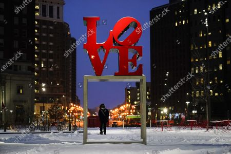 """Person wearing a face mask as a precaution against the coronavirus walks during a winter storm near the Robert Indiana sculpture """"LOVE"""" at John F. Kennedy Plaza, commonly known as Love Park, in Philadelphia"""