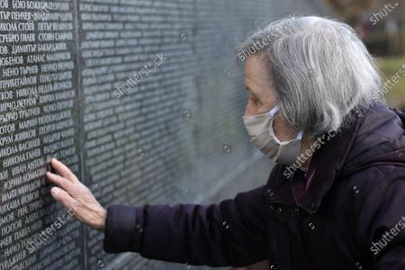 A woman touches Victims of Communism Memorial monument inscribed with names of victims of the communist rule in Bulgaria. The country marks the Day of Remembrance and Respect to victims of the communist rule which ended in 1989.