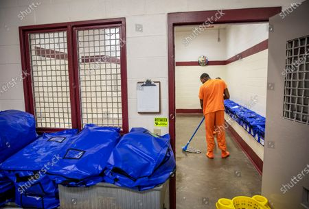 A detainee mops the floor at the intake station at the Stewart Detention Center in Lumpkin, Ga. Federal authorities said a 57-year-old Mexican man who was being held in federal immigration detention at the center in southwest Georgia died, from complications of COVID-19