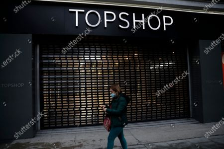Stock Picture of Woman wearing a face mask to curb the spread of coronavirus walks past a closed brach of Topshop on Oxford Street in London, during England's third national lockdown since the coronavirus outbreak began. Online fashion seller Asos has bought Topshop, which once boasted designs by Kate Moss and Beyonce, along with three other brands for 265 million pounds ($363 million) as rivals scoop up bargains after the collapse of Britain's Arcadia retail group. The deal, announced Monday, puts thousands of jobs at risk because Asos acquired the Topshop, Topman, Miss Selfridge's and HIIT brands but none of their stores