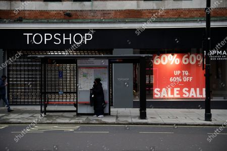 Woman wearing a face mask to curb the spread of coronavirus waits in a bus stop outside a closed brach of Topshop on Oxford Street, in London, during England's third national lockdown since the coronavirus outbreak began. Online fashion seller Asos has bought Topshop, which once boasted designs by Kate Moss and Beyonce, along with three other brands for 265 million pounds ($363 million) as rivals scoop up bargains after the collapse of Britain's Arcadia retail group. The deal, announced Monday, puts thousands of jobs at risk because Asos acquired the Topshop, Topman, Miss Selfridge's and HIIT brands but none of their stores