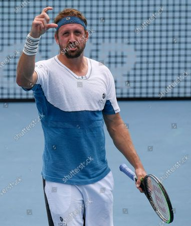 United States' Tennys Sandgren reacts during his match against Australia's John-Patrick Smith at a tuneup tournament ahead of the Australian Open tennis championships in Melbourne, Australia