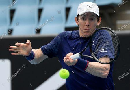 Australia's John-Patrick Smith makes a forehand return to United States' Tennys Sandgren during a tuneup tournament ahead of the Australian Open tennis championships in Melbourne, Australia
