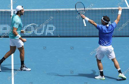 Italy's Matteo Berritini, left, and Fabio Fognini celebrate a point win against Austria's Dennis Novak and Dominic Thiem during their ATP Cup match in Melbourne, Australia