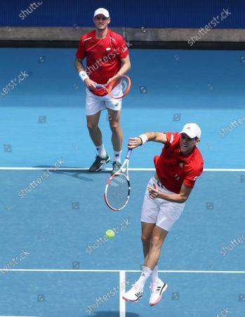 Austria's Dennis Novak and Dominic Thiem, right, in action against Italy's Matteo Berritini and Fabio Fognini during their ATP Cup match in Melbourne, Australia