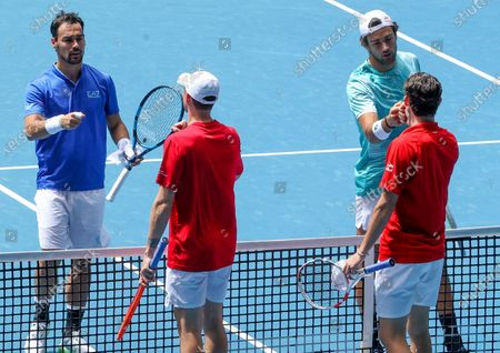 Italy's Matteo Berritini, top right, and Fabio Fognini, left, are congratulated by Austria's Dennis Novak, right, and Dominic Thiem, second left, after their ATP Cup match in Melbourne, Australia