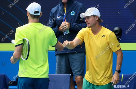 Australia's John Millman, left, gestures with team captain Lleyton Hewitt, right, during his ATP Cup match against Spain's Pablo Carreno Busta in Melbourne, Australia