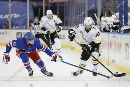 New York Rangers' Adam Fox (23) skates with the puck as Pittsburgh Penguins' Jason Zucker (16) gives chase during the first period of an NHL hockey game at Madison Square Garden, in New York