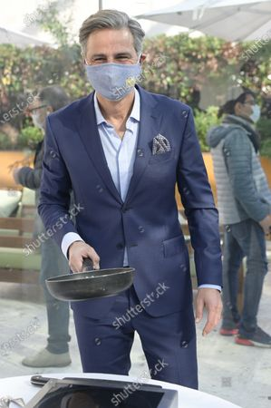 Stock Image of Beppe Convertini wearing a mask is seen holding a cooking pan during the Dispensa Stellata fourth edition event. Esposizioni Restaurant at Exposition Palace, the fourth edition of the format against food waste promoted by the Consorzio Zampone and Cotechino Modena IGP. It presents a new, tasty and original recipes, ideal for disposing of the pantry but with a touch of creativity and a nod to the EU legislation against food waste.