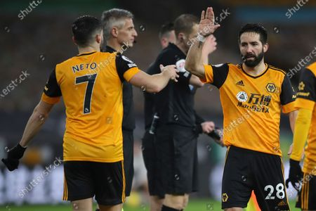 Wolverhampton Wanderers' Joao Moutinho, right, celebrates with Wolverhampton Wanderers' Pedro Neto at the end of the English Premier League match between Wolverhampton Wanderers and Arsenal at the Molineux Stadium in Wolverhampton, England