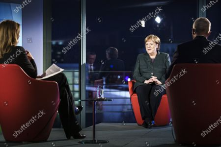 Stock Picture of German Chancellor Angela Merkel (C) appears at the German public ARD television channel for an interview, Berlin, Gwrmany, 02 February 2021. Merkel was interviewed by TV journalists Rainald Becker und Tina Hassel for the program 'Farbe bekennen' (state your opinion).