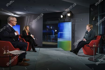 German Chancellor Angela Merkel (R) appears at the German public ARD television channel for an interview, Berlin, Gwrmany, 02 February 2021. Merkel was interviewed by TV journalists Rainald Becker und Tina Hassel (C) for the program 'Farbe bekennen' (state your opinion).