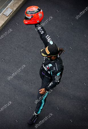 NYRBURGRING, GERMANY - OCTOBER 11: Lewis Hamilton, Mercedes-AMG Petronas F1, 1st position, on the podium with the helmet of Michael Schumacher that was presented to him by Mick Schumacher upon equalling Michaels record number of 91 wins during the Eifel GP at NYrburgring on Sunday October 11, 2020, Germany. (Photo by Zak Mauger / LAT Images)