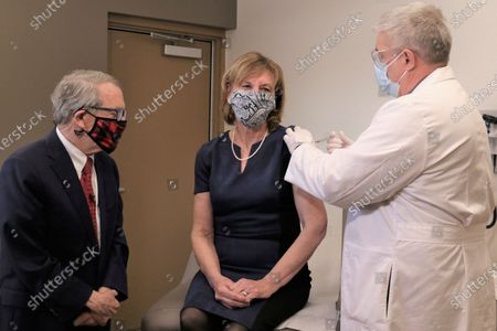Ohio Governor Mike DeWine, left, looks on as first lady Fran DeWine receives her COVID-19 vaccination from Dr. Kevin Sharrett, Tuesday, 2, 2021, in Jamestown, Ohio. The DeWines became eligible to receive their first shot this week as vaccinations are now open to Ohioans age 70 and above