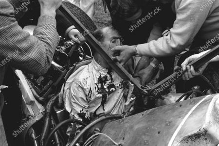 Stock Image of Stirling Moss (GBR) in the remains of the Lotus 18 Climax, the accident that ended his career at St Marys corner