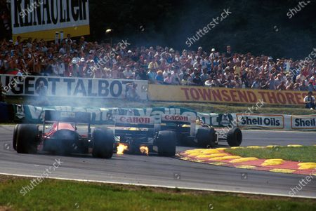 Stock Image of The flame spitting Williams FW11 of Nigel Mansell (GBR) leads the smoking Ferrari F186.British GP, Brands Hatch,  13th July 1986