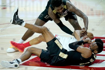 Stock Picture of Maryland guard Aaron Wiggins, center, competes for a loose ball with Purdue forward Trevion Williams, top, and forward Aaron Wheeler during the first half of an NCAA college basketball game, in College Park