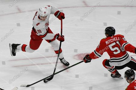 Carolina Hurricanes center Martin Necas (88) shoots the puck past Chicago Blackhawks defenseman Ian Mitchell (51) during the first period of an NHL hockey game, in Chicago