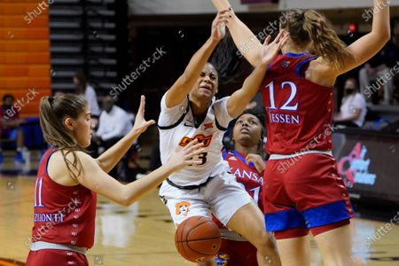 Oklahoma State guard Lauren Fields, center, loses the ball as she is fouled from behind by Kansas guard Brooklyn Mitchell, between Kansas forwards Ioanna Chatzileonti (11) and Katrine Jessen (12) during the second half of an NCAA college basketball game, in Stillwater, Okla