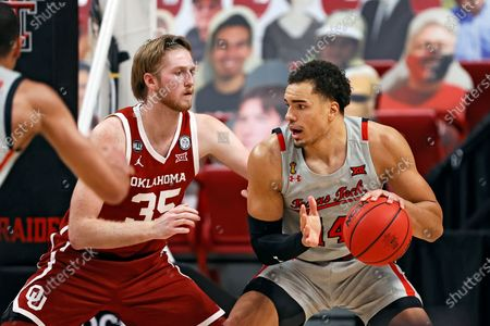Texas Tech's Marcus Santos-Silva (14) dribbles the ball around Oklahoma's Brady Manek (35) during the first half of an NCAA college basketball game, in Lubbock, Texas