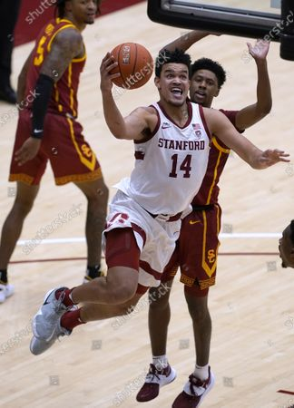 Stanford forward Spencer Jones (14) drives to the basket against Southern California guard Tahj Eaddy (2) during the second half of an NCAA college basketball game in Stanford, Calif., . Southern California won 72-66