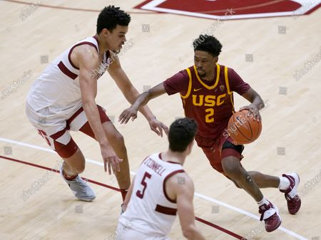 Southern California guard Tahj Eaddy (2) moves the ball between Stanford forward Spencer Jones, left, and guard Michael O'Connell (5) during the second half of an NCAA college basketball game in Stanford, Calif., . Southern California won 72-66