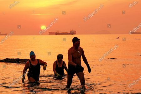 Stock Picture of A winter swimming enthusiast swims in Jiazi Bay of Ganjingzi District in Dalian, Liaoning province, Feb 3, 2021. On that day, the first of the 24 solar terms, the Start of Spring, marks the beginning of a new cycle of all living things.