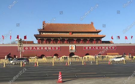 Traffic passes Tiananmen Square's North Rostrum, featuring a giant portrait of former chairman Mao Zedong, in Beijing on Wednesday, February 3, 2021.  Tiananmen Square, one of China's most important and visited historical sites, has largely remained empty due to a partial lockdown because of the threat of Covid-19 in the capital.