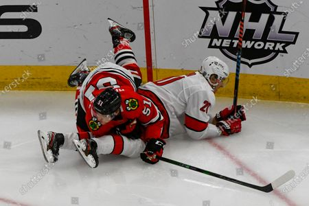 Chicago Blackhawks defenseman Ian Mitchell (51) and Carolina Hurricanes right wing Sebastian Aho (20) during the third period of an NHL hockey game, in Chicago