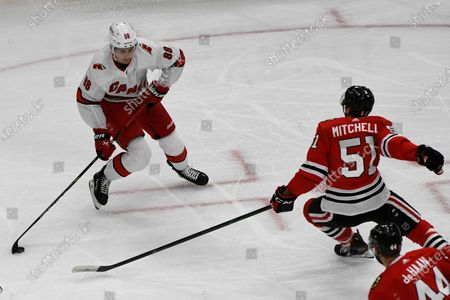 Carolina Hurricanes center Martin Necas (88) moves the puck against Chicago Blackhawks defenseman Ian Mitchell (51) during the first period of an NHL hockey game, in Chicago