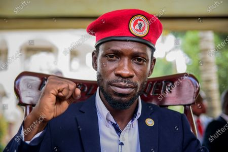 Opposition presidential challenger Bobi Wine, whose real name is Kyagulanyi Ssentamu, gestures as he speaks to the media outside his house after government soldiers withdrew from it, in Magere, near Kampala, in Uganda. Uganda's President Yoweri Museveni in Feb. 2021 has ordered the suspension of the multimillion-dollar Democratic Governance Facility fund backed by European nations that supports the work of local groups focusing on democracy and good governance