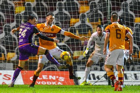 Stock Image of Lawrence Shankland (#24) of Dundee Utd FC gets to the ball ahead of Stephen O'Donnell (#33) of Motherwell FC during the SPFL Premiership match between Motherwell and Dundee United at Fir Park, Motherwell