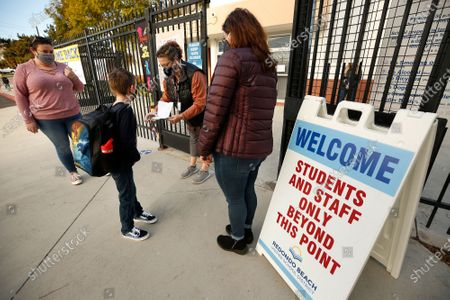 First grade student Brandon Blaco with his Mom Brandy Parras, left, checks in with Gabrielle Flaum and Firoozeh Borjian, right, before having his temperature taken when he arrives at Alta Vista Elementary School for the second day of classes as Redondo Beach Unified School district has welcomed back some of its K-2 students this week through a waiver. Alta Vista Elementary School on Tuesday, Feb. 2, 2021 in Redondo Beach, CA. (Al Seib / Los Angeles Times).