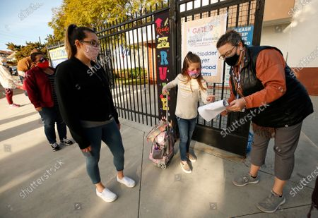 First grade student Braylen Coleman with her Mom Aja Coleman, left checks in with school staffer Gabrielle Flaum, right, as she arrives at Alta Vista Elementary School for the second day of classes as Redondo Beach Unified School district has welcomed back some of its K-2 students this week through a waiver. Alta Vista Elementary School on Tuesday, Feb. 2, 2021 in Redondo Beach, CA. (Al Seib / Los Angeles Times).