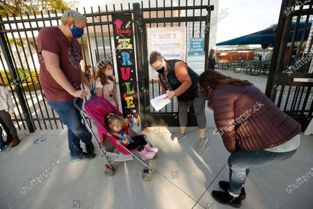 Stock Image of Anton Jacobs, left, with 2-year-old Zoe in stroller brings first grade daughter Carley Jacobs to check in with school staff Gabrielle Flaum and Firoozeh Borjian, right, at Alta Vista Elementary School as students arrive for the second day of classes as Redondo Beach Unified School district has welcomed back some of its K-2 students this week through a waiver. Alta Vista Elementary School on Tuesday, Feb. 2, 2021 in Redondo Beach, CA. (Al Seib / Los Angeles Times).