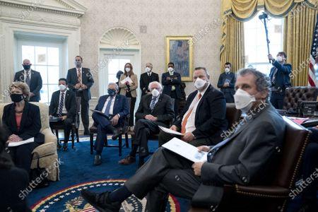 Stock Photo of From left: Senator Debbie Stabenow (D-M.I), Senator Brian Schatz (D-H.I.), Senator Bob Menendez (D-NJ), Senator Bernie Sanders (I-VT), Senator Jon Tester (D-MT), and Senator Sherrod Brown (D-OH) wear protective masks during a meeting with President Joe Biden, not pictured, in the Oval Office of the White House